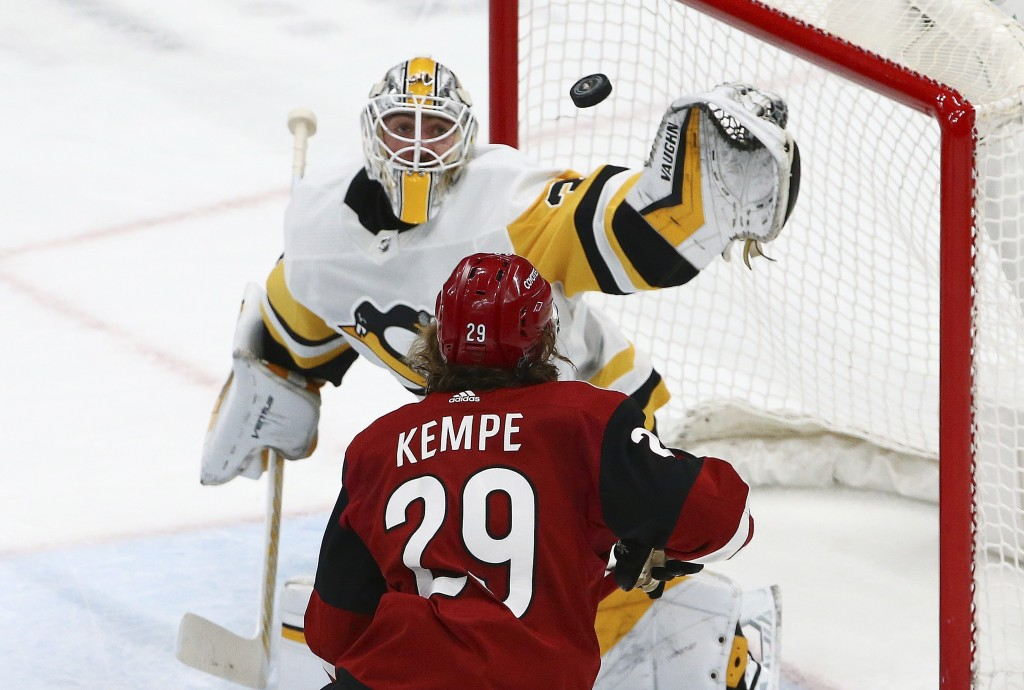 Pittsburgh Penguins goaltender Matt Murray, top, reaches out to make a glove save on a shot as Arizona Coyotes right wing Mario Kempe (29) waits for a...