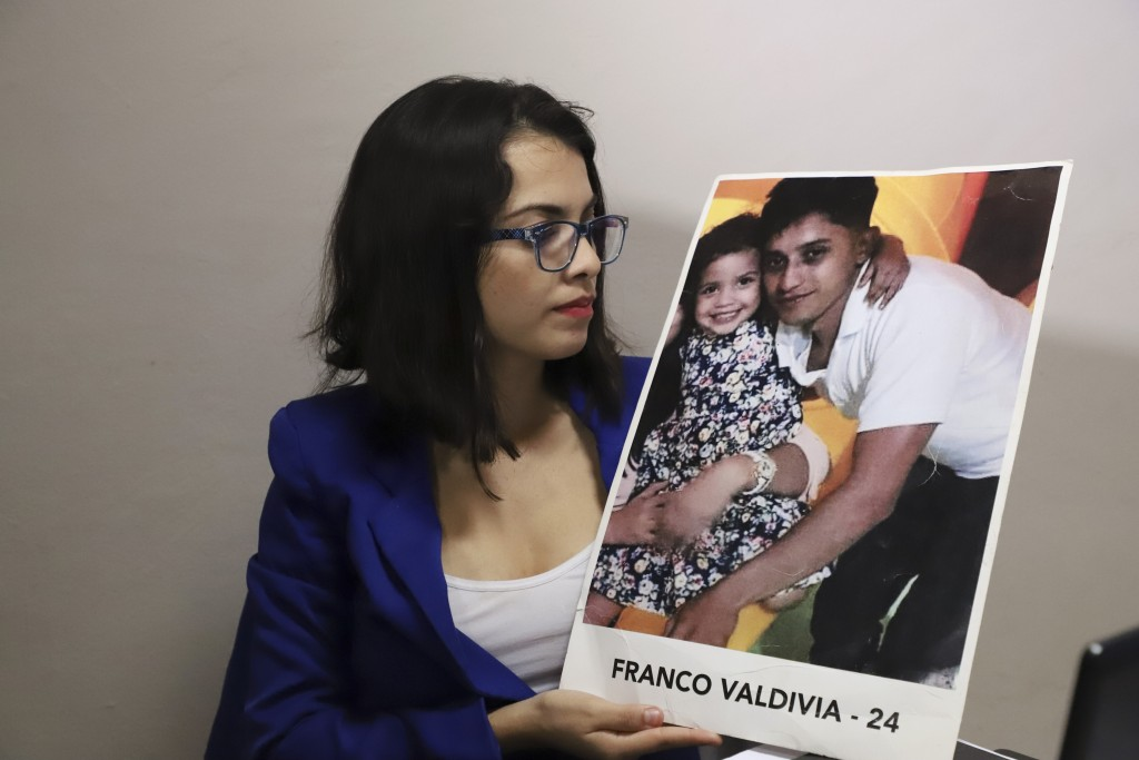 In this Jan. 8, 2019 photo, 28-year-old lawyer Francys Valdivia Machado, president of the Madres de Abril Association, holds a picture of her 24-year-...
