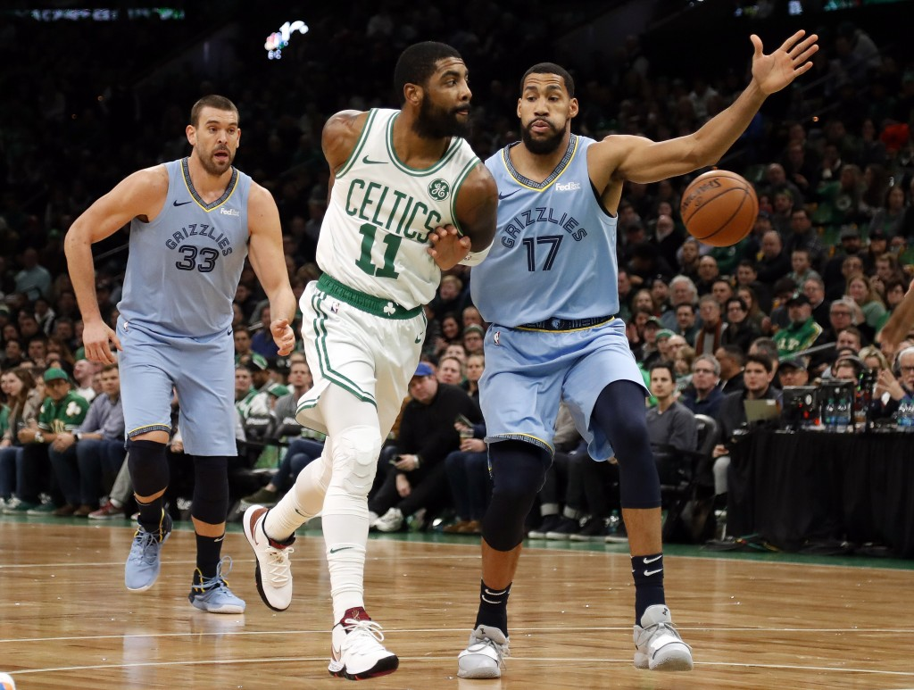 Boston Celtics' Kyrie Irving throws a behind-the-back pass past Memphis Grizzlies' Garrett Temple (17) during the first quarter of an NBA basketball g
