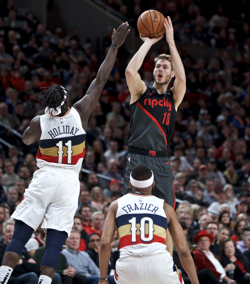 Portland Trail Blazers forward Jake Layman shoots over New Orleans Pelicans guard Jrue Holiday, left, and guard Tim Frazier, bottom, during the second