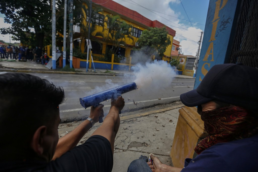 FILE - In this June 12, 2018 file photo, anti-government protesters fire homemade mortars at police and government supporters in Jinotepe, Nicaragua.