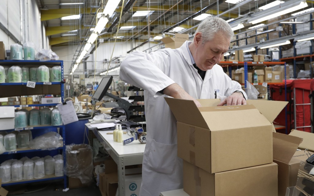 In this photo taken on Thursday, Jan. 17, 2019, Michael O'Brien, Supervisor at Clarity_The Soap Co. prepares an order at the premises in London. Amid
