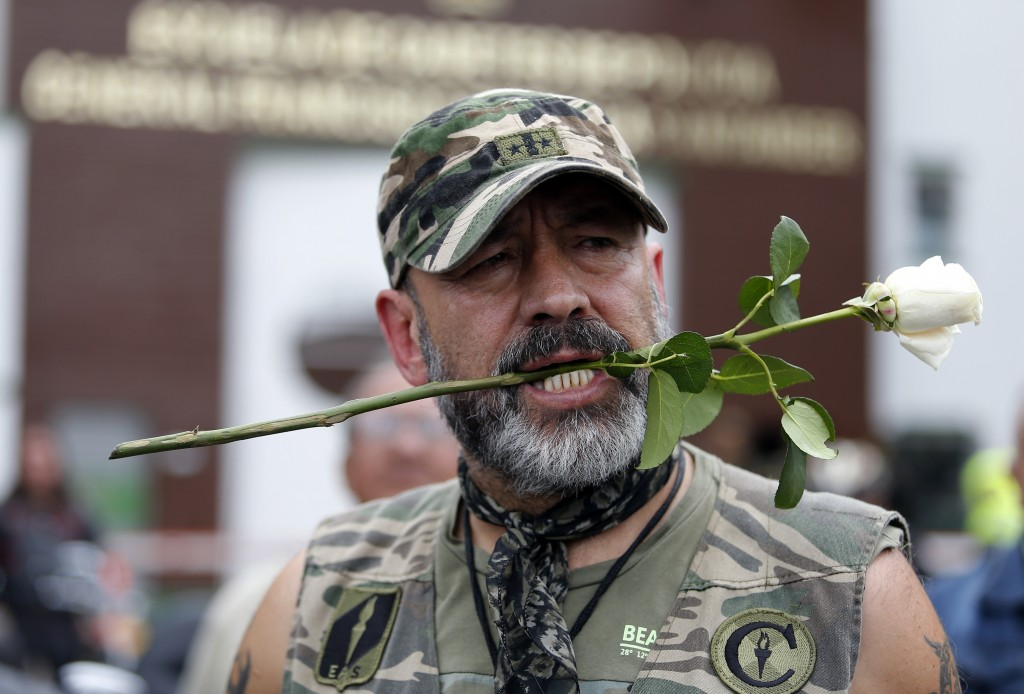 A man holds a rose in his mouth before he placing it on an impromptu memorial outside the General Francisco de Paula Santander Police Academy, a day a...