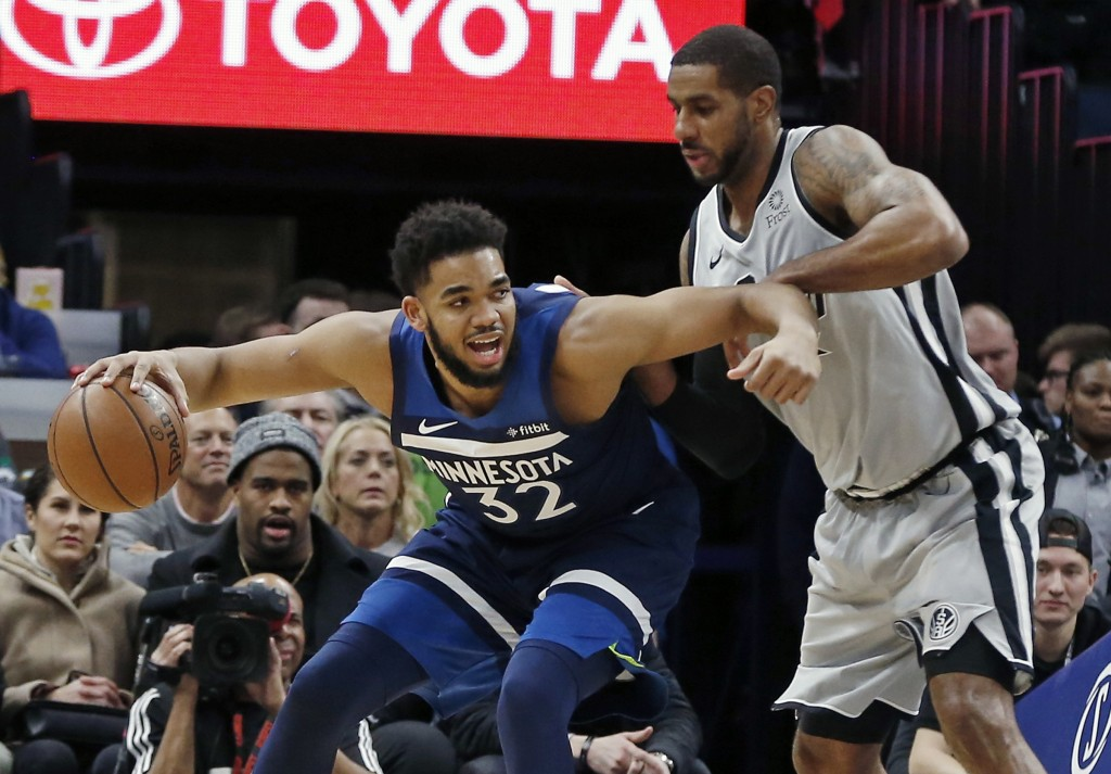 Minnesota Timberwolves' Karl-Anthony Towns, left, keeps the ball at arm's length from San Antonio Spurs' LaMarcus Aldridge in the first half of an NBA