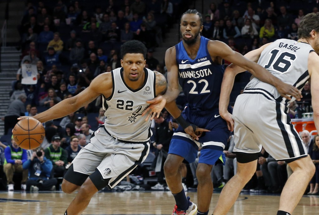 San Antonio Spurs' Rudy Gay, left, drives as Minnesota Timberwolves' Andrew Wiggins, center tries to get around Pau Gasol of Spain in the first half o...