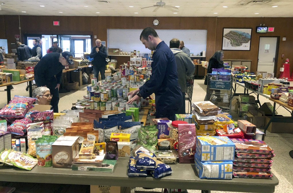 In this Thursday, Jan. 17, 2019 photo, a member of the U.S. Coast Guard arranges donated canned goods at a pop-up food pantry at the U.S. Coast Guard ...