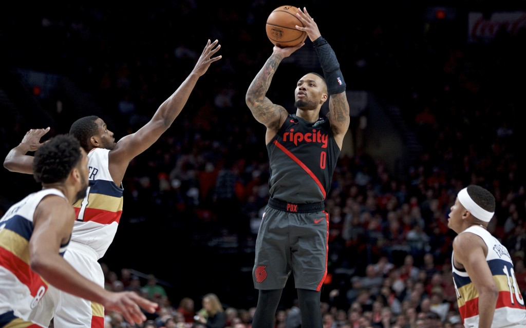 Portland Trail Blazers guard Damian Lillard shoots between New Orleans Pelicans forward Darius Miller, left, and guard Tim Frazier, right, during the