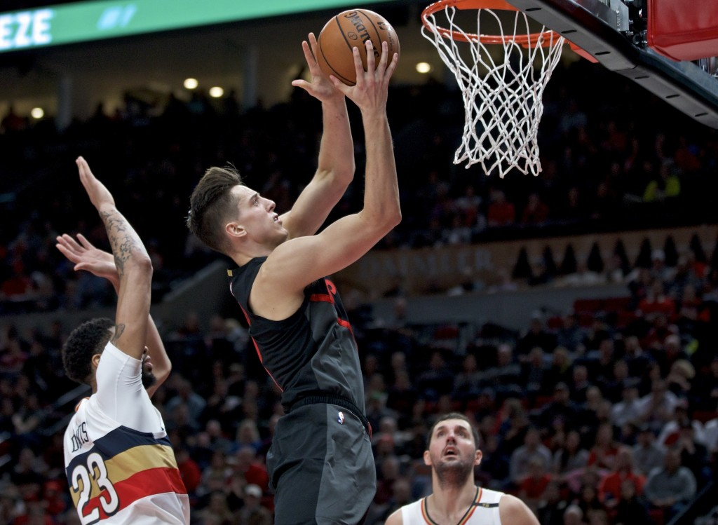 Portland Trail Blazers forward Zach Collins, right, shoots next to New Orleans Pelicans forward Anthony Davis, left, during the second half of an NBA