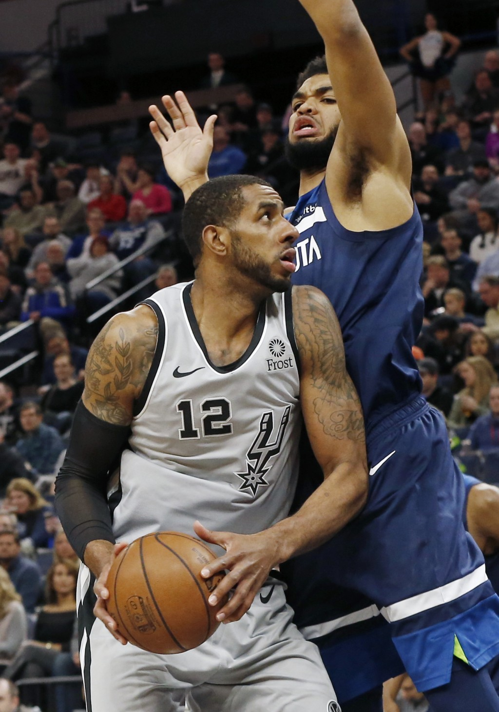 San Antonio Spurs' LaMarcus Aldridge, left, eyes the basket as Minnesota Timberwolves' Karl-Anthony Towns defends in the first half of an NBA basketba...