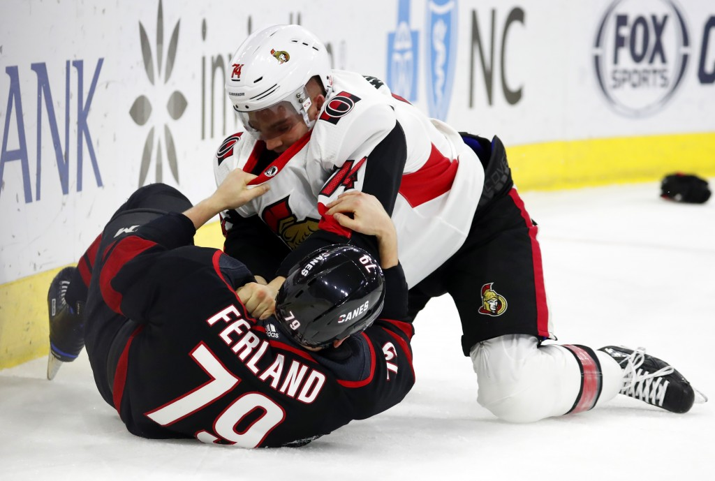 Ottawa Senators' Mark Borowiecki (74) tussles with Carolina Hurricanes' Micheal Ferland (79) during the first period of an NHL hockey game Friday, Jan