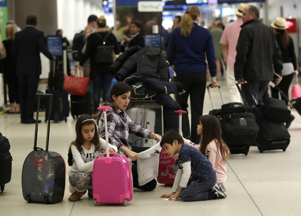 Travelers organize their luggage before entering a security checkpoint at Miami International Airport, Friday, Jan. 18, 2019, in Miami. The three-day