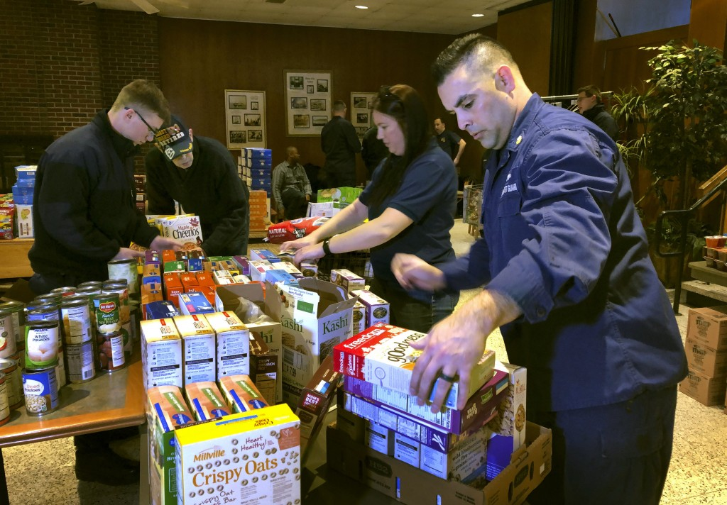 In this Thursday, Jan. 17, 2019 photo, U.S. Coast Guard Culinary Specialist Jerry Wright, right, and Petty Officer 2nd Class Lauren Laughlin, second f...