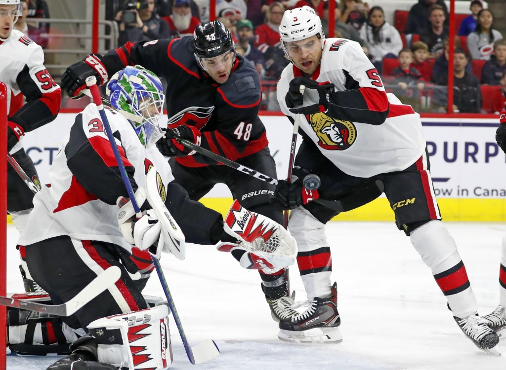 Carolina Hurricanes' Jordan Martinook (48) works between Ottawa Senators goaltender Anders Nilsson (31) and Senators' Cody Ceci (5) during the first p...