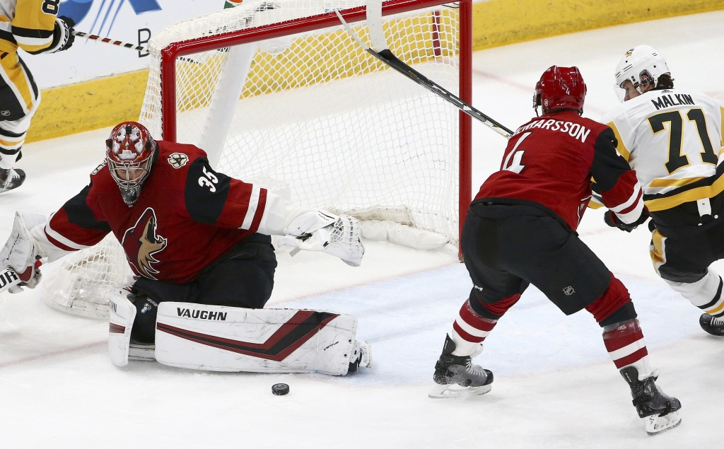 Arizona Coyotes goaltender Darcy Kuemper (35) makes a save as Coyotes defenseman Niklas Hjalmarsson (4) shoves Pittsburgh Penguins center Evgeni Malki...