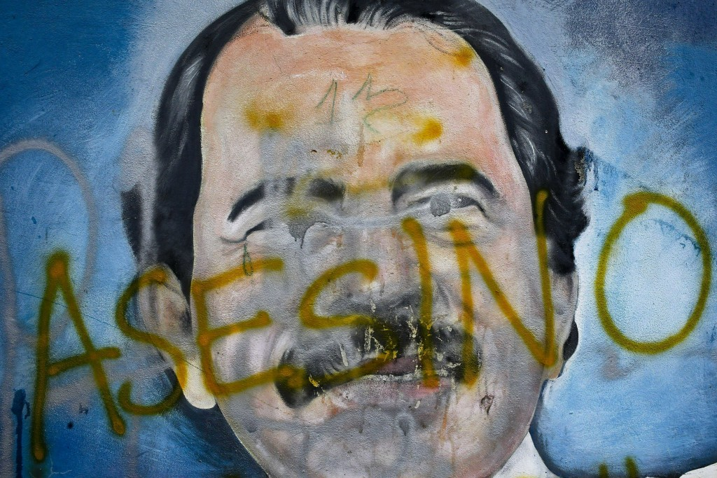 """FILE - In this May 26, 2018 file photo, the Spanish word for """"Murderer"""" covers a mural of Nicaragua's President Daniel Ortega, as part of anti-governm"""