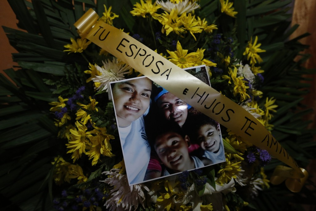 """FILE - In this May 3, 2018 file photo, a floral arrangement with the words in Spanish """"Your wife and children love you"""" stands during the funeral for ..."""