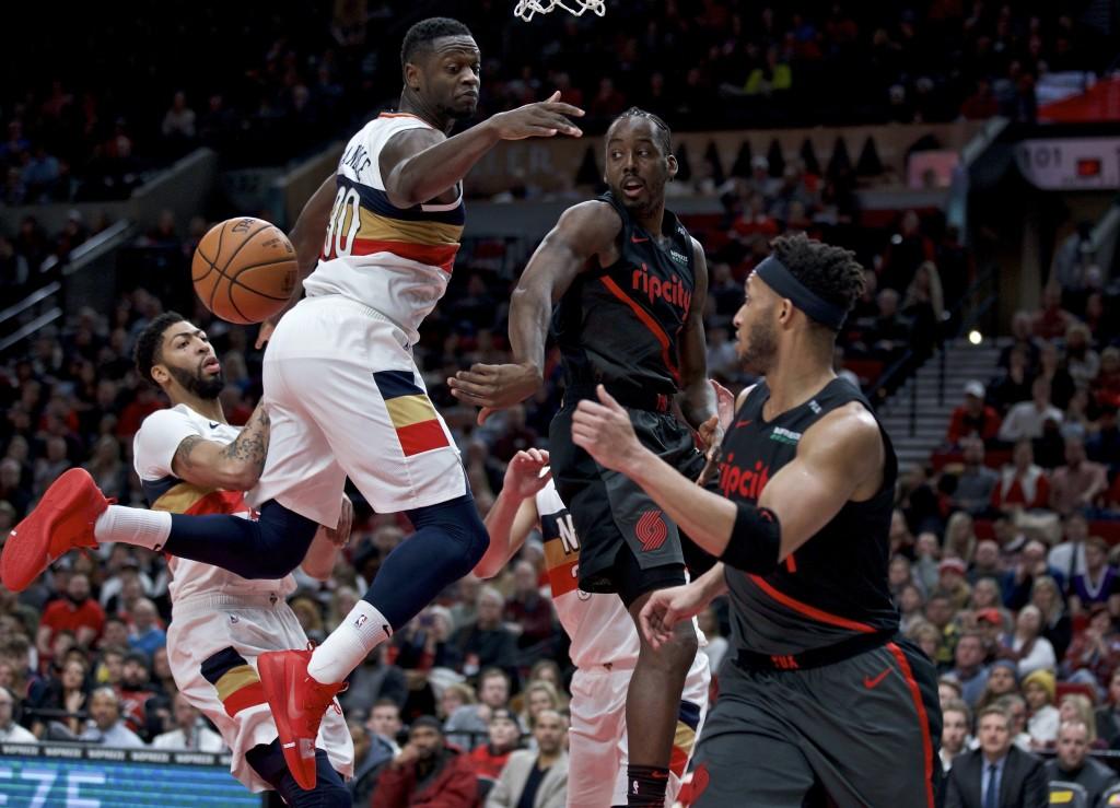 Portland Trail Blazers forward Al-Farouq Aminu, center, passes around New Orleans Pelicans forward Julius Randle during the second half of an NBA bask...