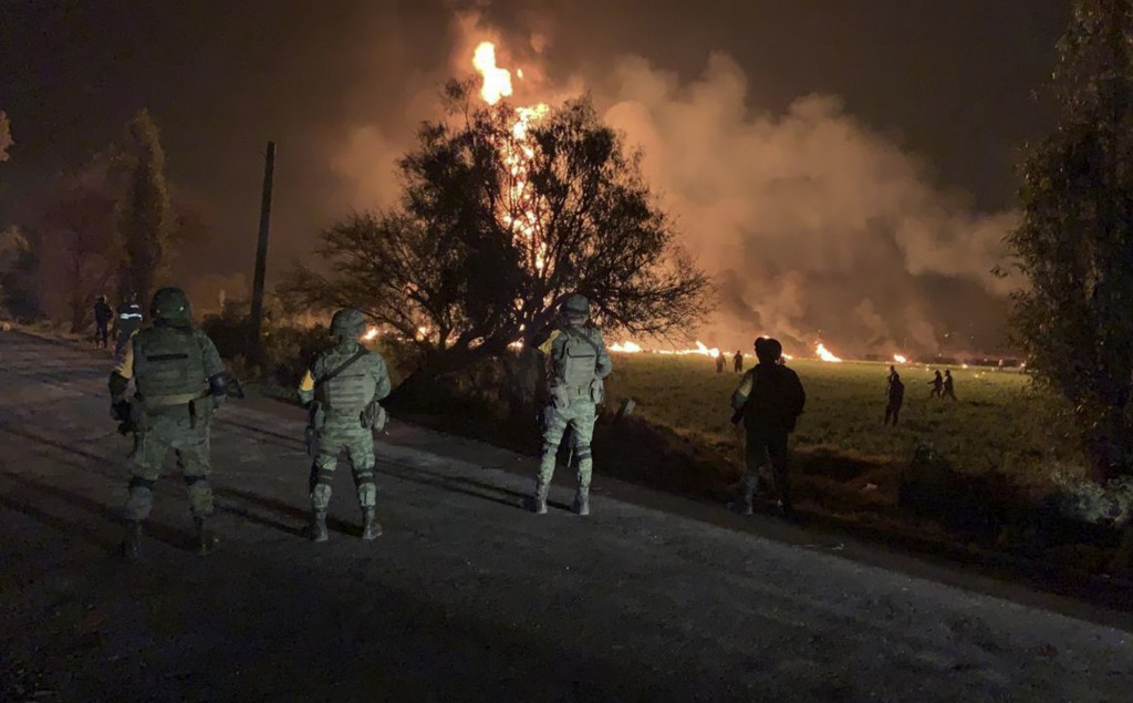 In this image provided by the Secretary of National Defense, soldiers guard the area by an oil pipeline explosion in Tlahuelilpan, Hidalgo state, Mexi