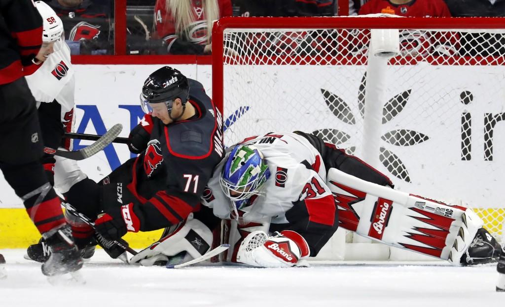 Carolina Hurricanes' Lucas Wallmark (71) collides with Ottawa Senators goaltender Anders Nilsson (31) during the third period of an NHL hockey game Fr...