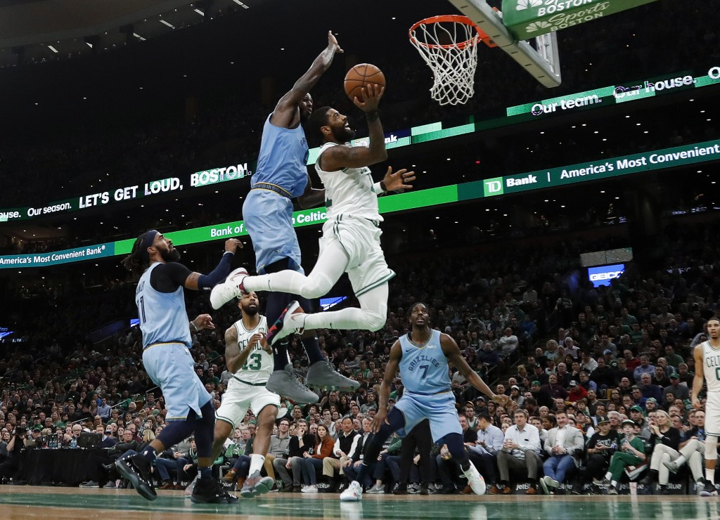 Boston Celtics' Kyrie Irving goes to the basket past Memphis Grizzlies' JaMychal Green during the second quarter of an NBA basketball game Friday, Jan