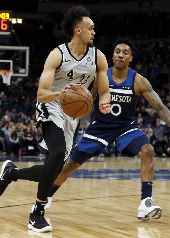San Antonio Spurs' Derrick White, left, drives around Minnesota Timberwolves' Josh Okogie of Nigeria in the first half of an NBA basketball game Frida