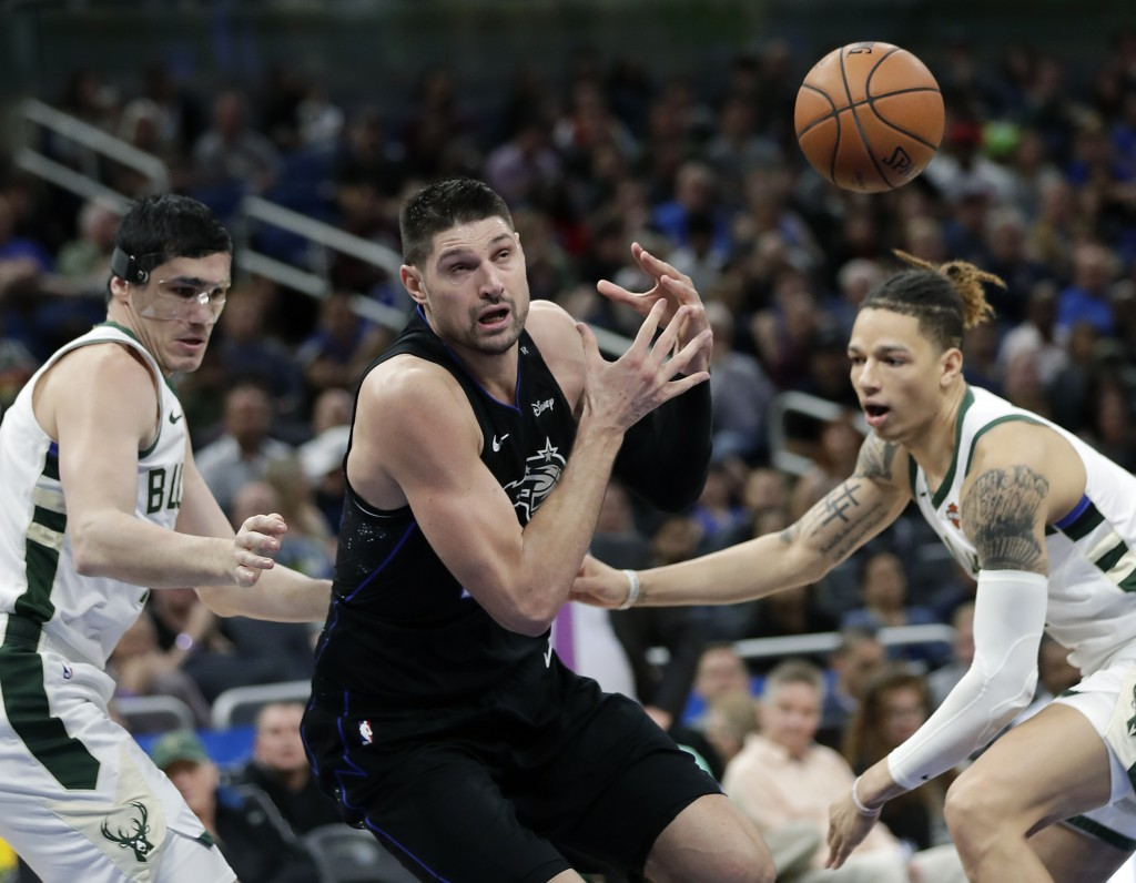 Orlando Magic's Nikola Vucevic loses his grip on the ball as he is fouled by Milwaukee Bucks' D.J. Wilson, right, during the first half of an NBA bask...