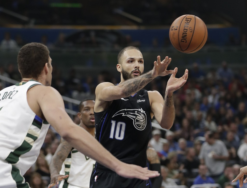 Orlando Magic's Evan Fournier (10) passes the ball as Milwaukee Bucks' Brook Lopez, left, defends during the first half of an NBA basketball game, Sat...