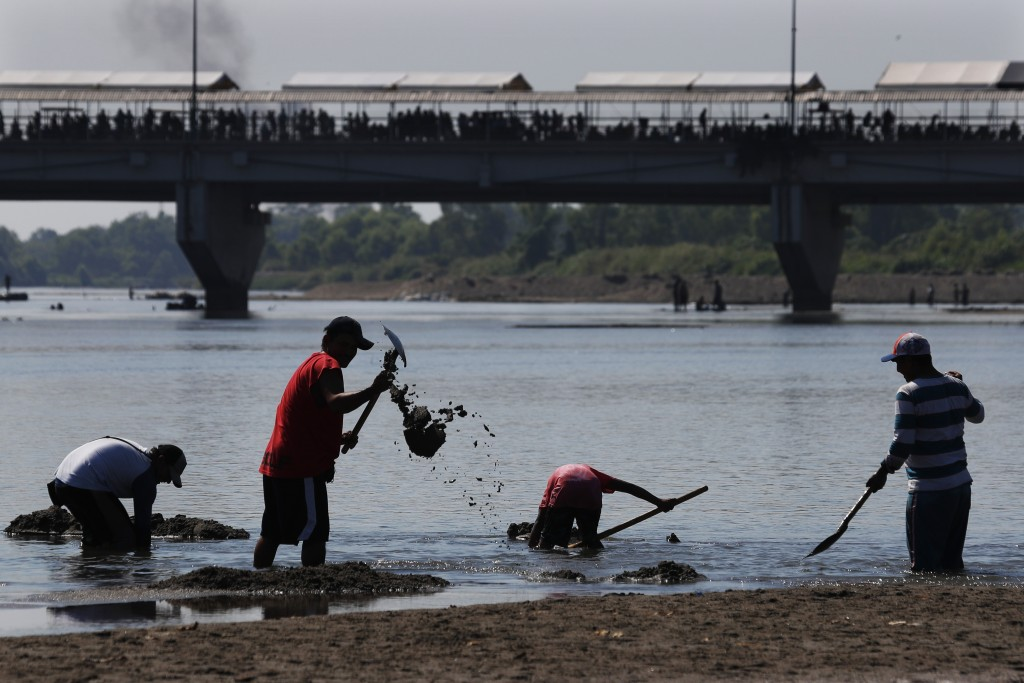 Workers clean the Suchiate River on the border between Guatemala and Mexico as Central American migrants wait to their migration issues at the bridge,