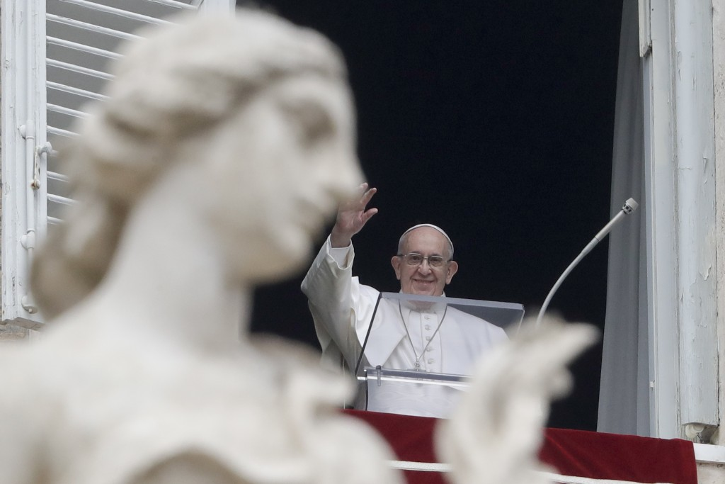 Pope Francis waves to the crowd gathered to attend the Angelus noon prayer he recited from the window of his studio overlooking St. Peter's Square, at