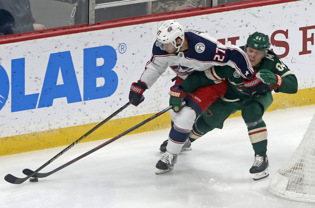Columbus Blue Jackets' Ryan Murray, left, and Minnesota Wild's Mikael Granlund skate after the puck in the first period of an NHL hockey game Saturday...