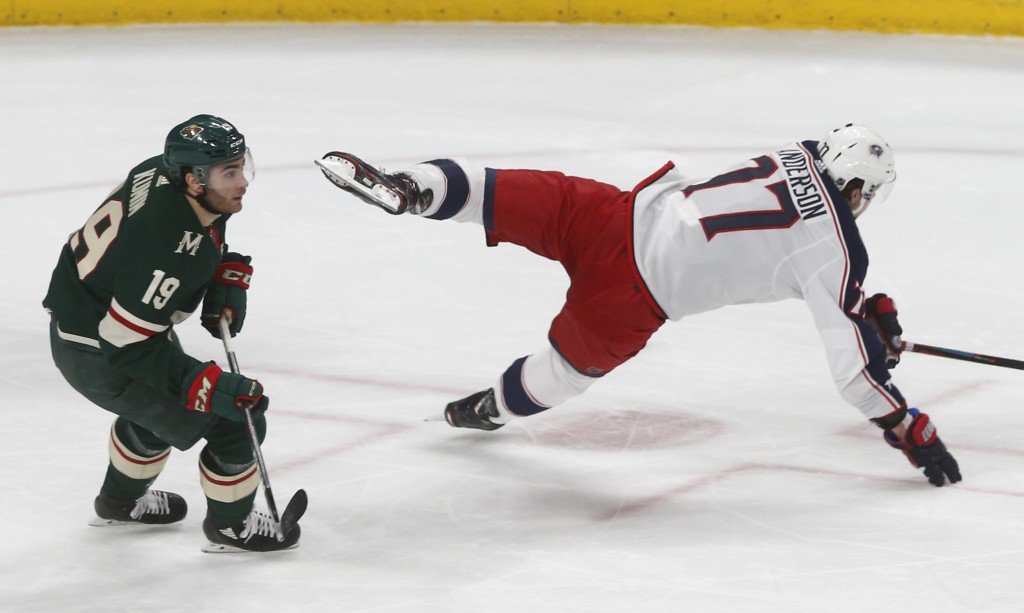 Minnesota Wild's Luke Kunin, left, continues skating as Columbus Blue Jackets' Josh Anderson loses his footing during the first period of an NHL hocke...