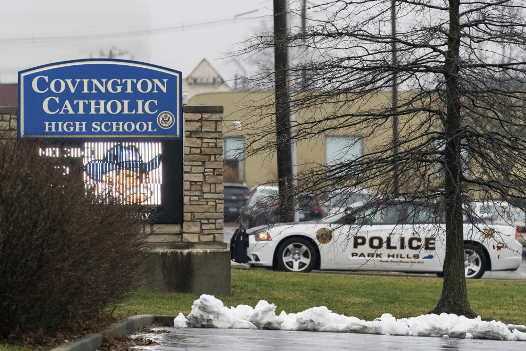 A police car sits at the entrance to Covington Catholic High School in Park Hills, Ky., Saturday, Jan 19, 2019. A diocese in Kentucky apologized Satur