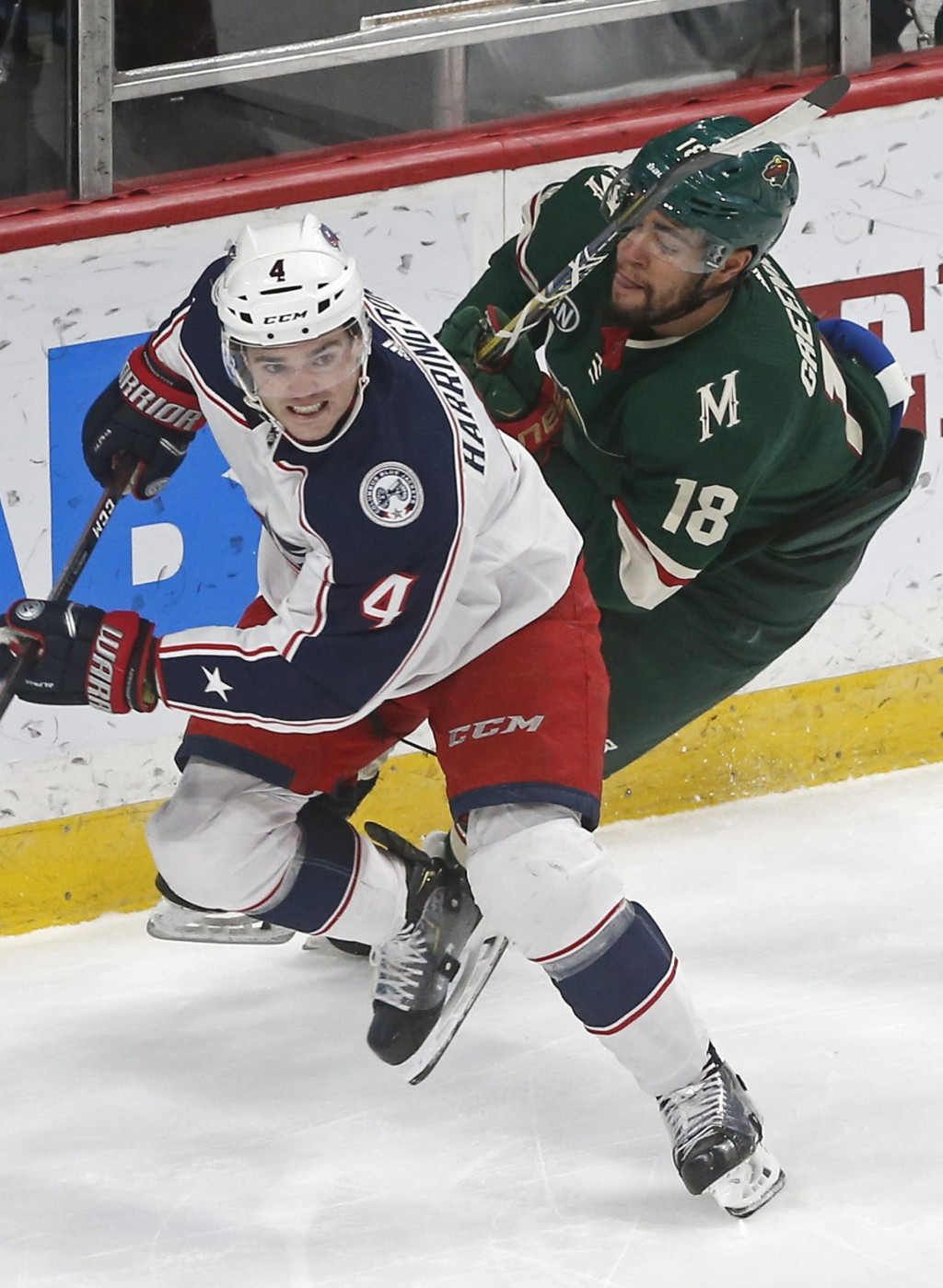 Columbus Blue Jackets' Scott Harrington, left, is pursued by Minnesota Wild's Jordan Greenway during the first period of an NHL hockey game Saturday, ...