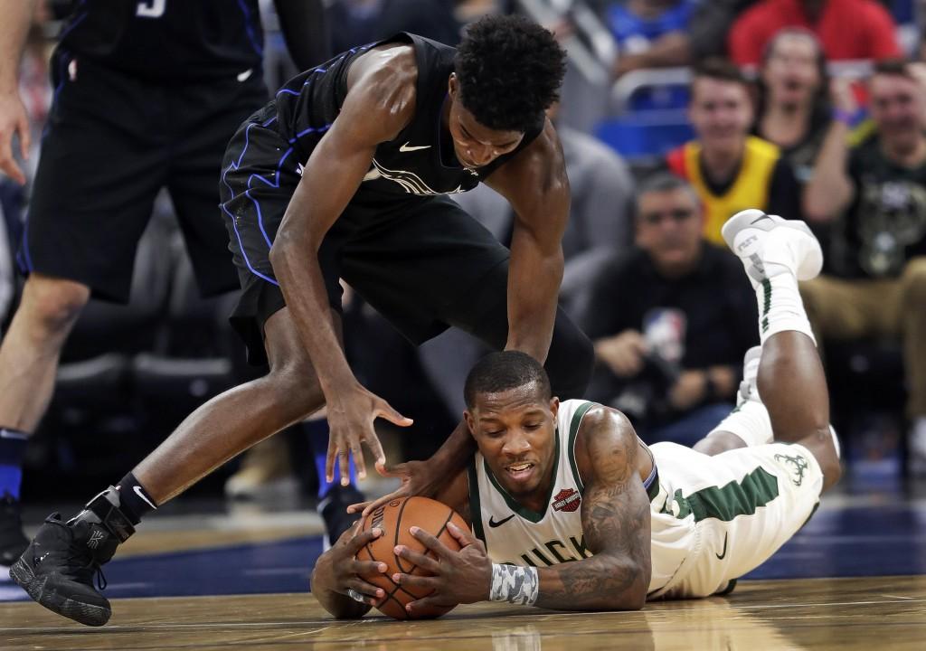 Orlando Magic's Jonathan Isaac, left, and Milwaukee Bucks' Eric Bledsoe go after a loose ball during the first half of an NBA basketball game, Saturda...