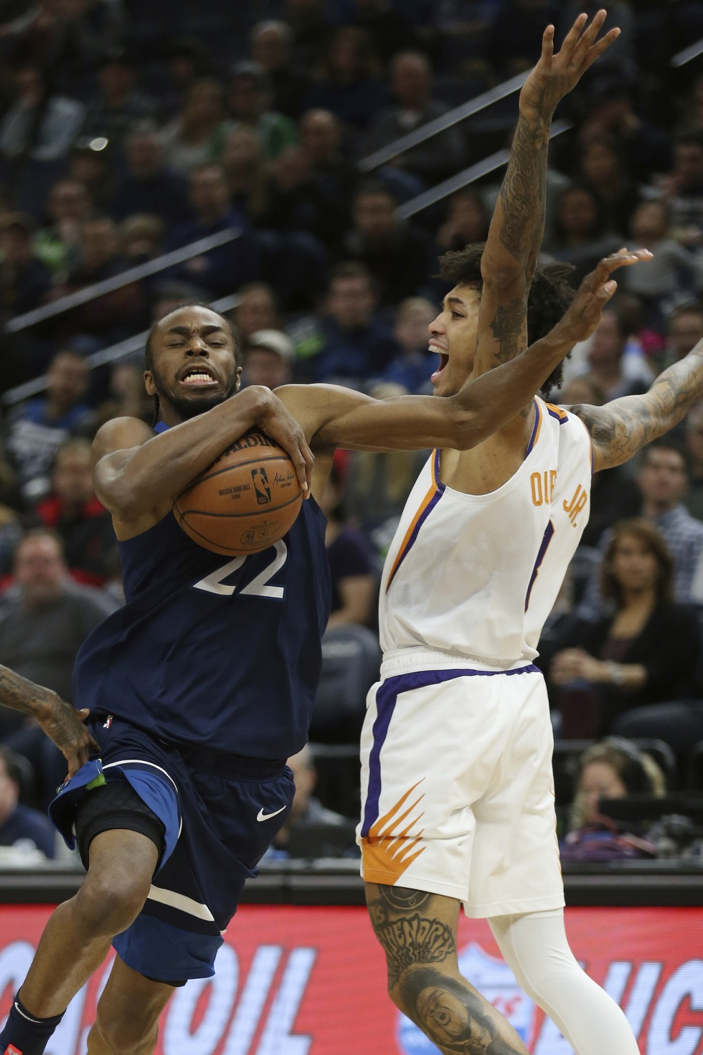 Minnesota Timberwolves' Andrew Wiggins drives the ball past Phoenix Suns' Devin Booker in the first half of an NBA basketball game Sunday, Jan. 20, 20...