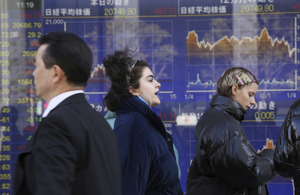 People walk by an electronic stock board of a securities firm in Tokyo, Monday, Jan. 21, 2019. Shares in Asia rose Monday, extending gains on Wall Str...
