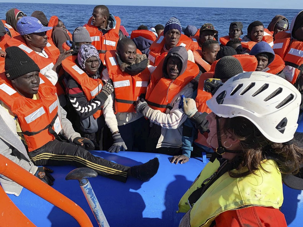 In this photo taken on Saturday, Jan. 19, 2019, rescued migrants are assisted by Sea-Watch rescue ship's personnel in the Mediterranean Sea. A private...