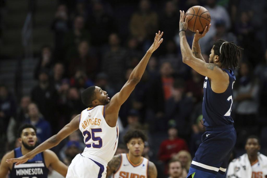 Minnesota Timberwolves' Derrick Rose shoots the game-winning shot over Phoenix Suns' Mikal Bridges in the first half of an NBA basketball game Sunday,...