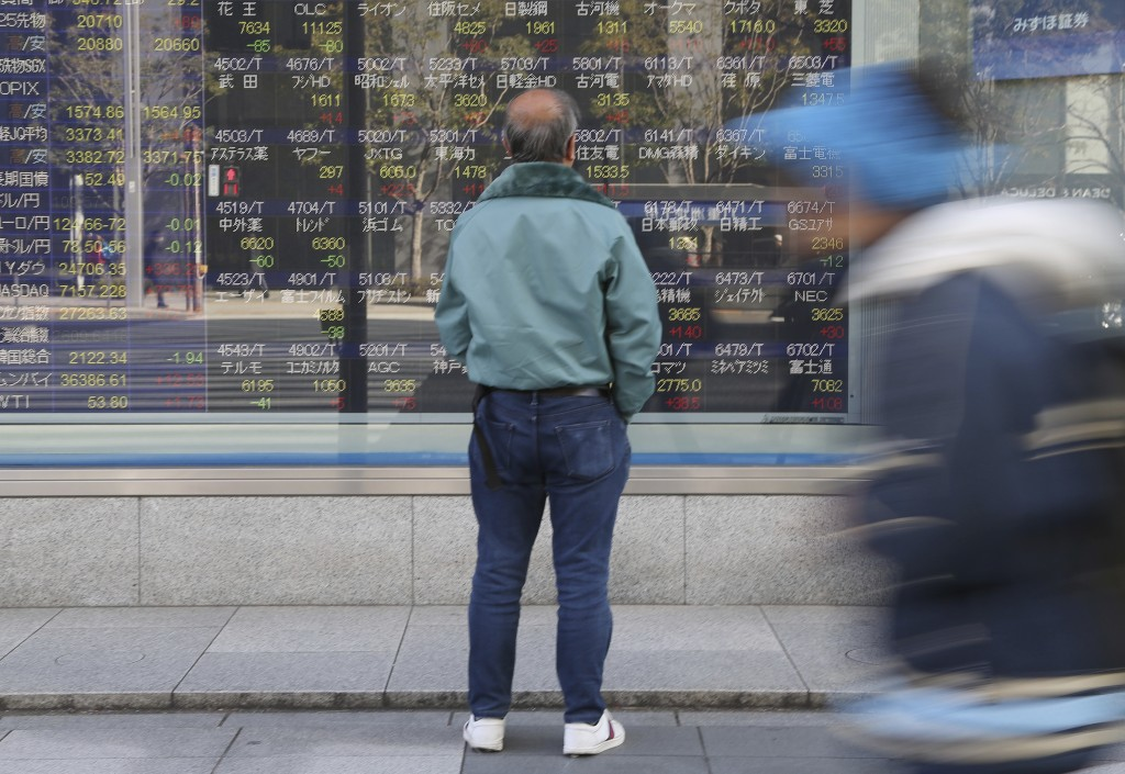 A man looks at an electronic stock board of a securities firm in Tokyo, Monday, Jan. 21, 2019. Shares in Asia rose Monday, extending gains on Wall Str...