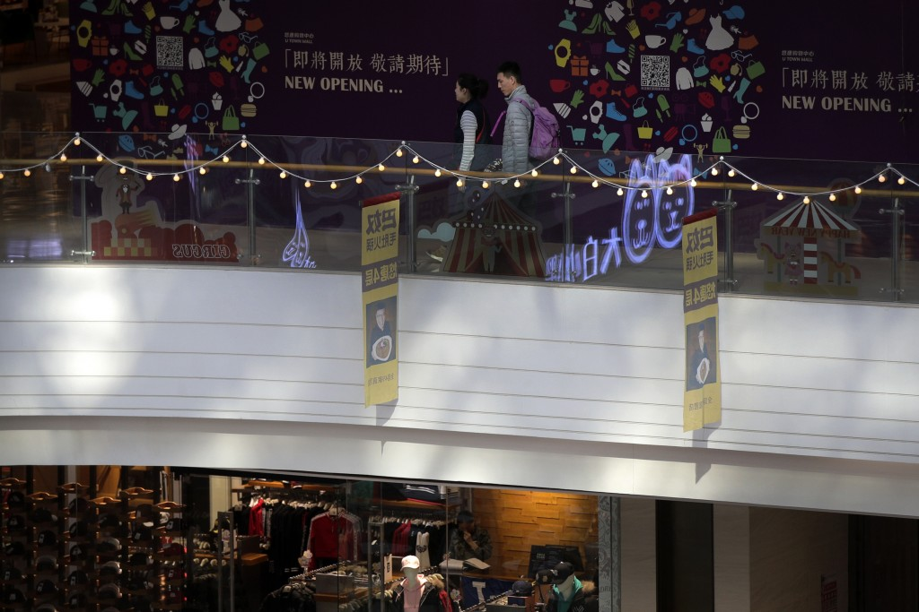 In this Jan. 20, 2019, photo, a Chinese couple walk by a vacant shop lot as a worker, below, waits for customers at a clothing shop at a shopping mall
