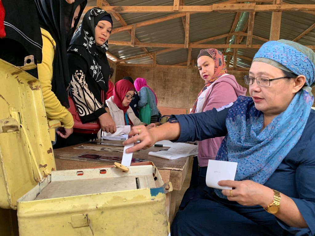 A Muslim woman casts her ballot in a referendum at the Marawi Sagonsongan elementary school-turned polling station in Marawi, Lanao del Sur province, ...