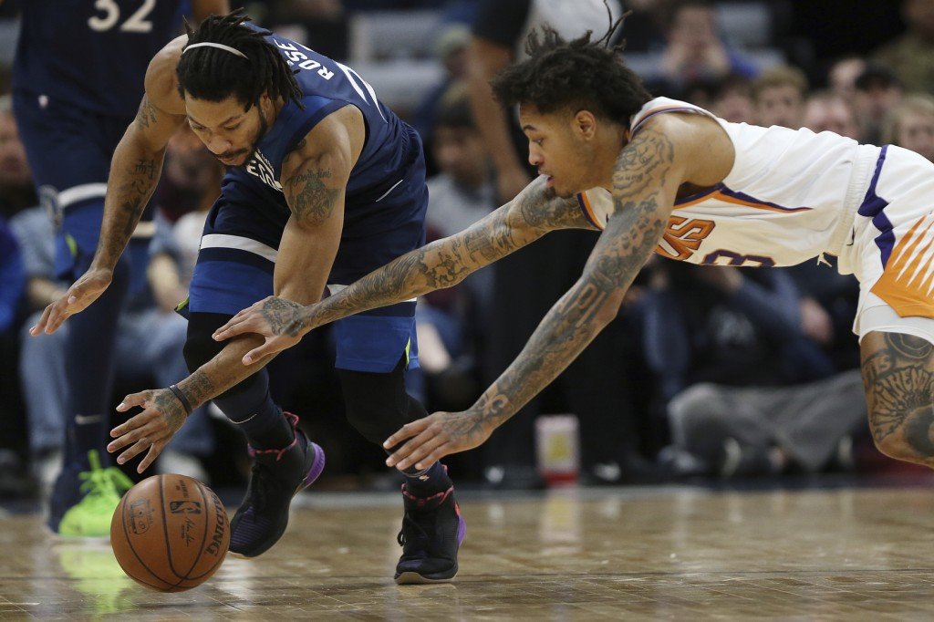 Minnesota Timberwolves' Derrick Rose and Phoenix Suns' Kelly Oubre Jr., go after a loose ball in the first half of an NBA basketball game Sunday, Jan....