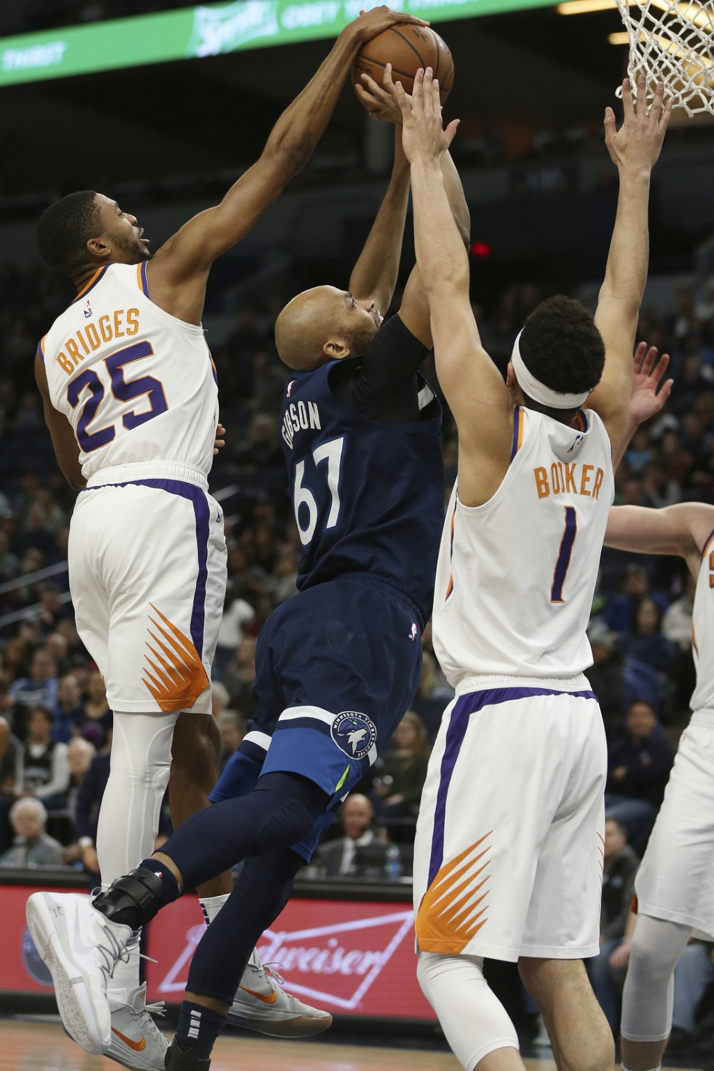 Minnesota Timberwolves' Taj Gibson tries to go up to the basket against Phoenix Suns' Mikal Bridges and Phoenix Suns' Devin Booker in the first half o...