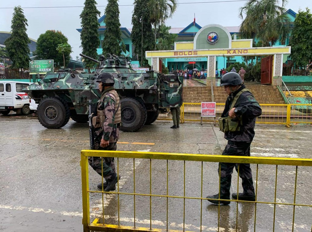 Soldiers walk near an armored personnel carrier parked outside the Saguiaran city hall in Lanao del Sur province, southern Philippines, Monday, Jan. 2...