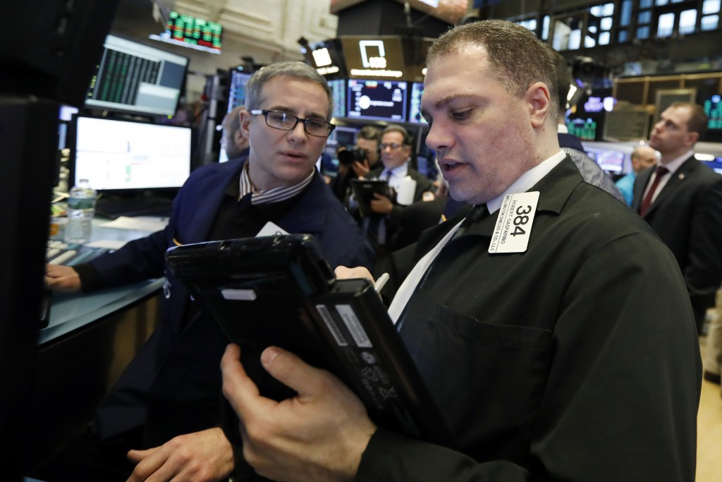 FILE- In this Jan. 18, 2019, file photo specialist Anthony Rinaldi, left, and trader Robert Gasparino work on the floor of the New York Stock Exchange...