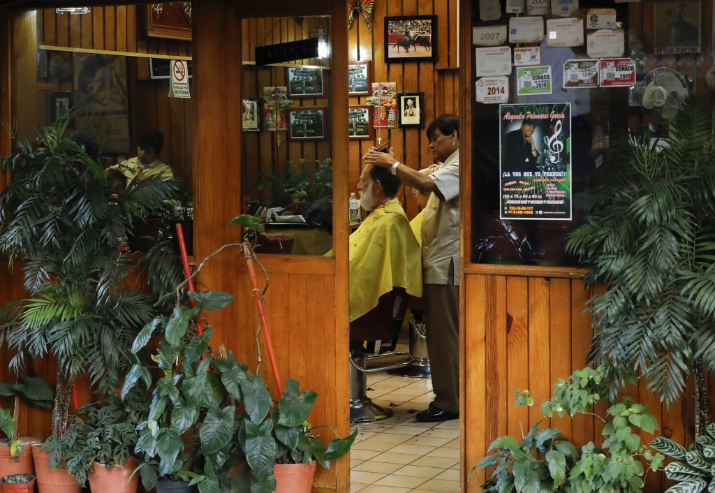 "A man gets his hair cut at a barbershop in the Roma Sur neighborhood of Mexico City, Wednesday, Dec. 19, 2018. News of Alfonso Cuaron's ""Roma"" being n"