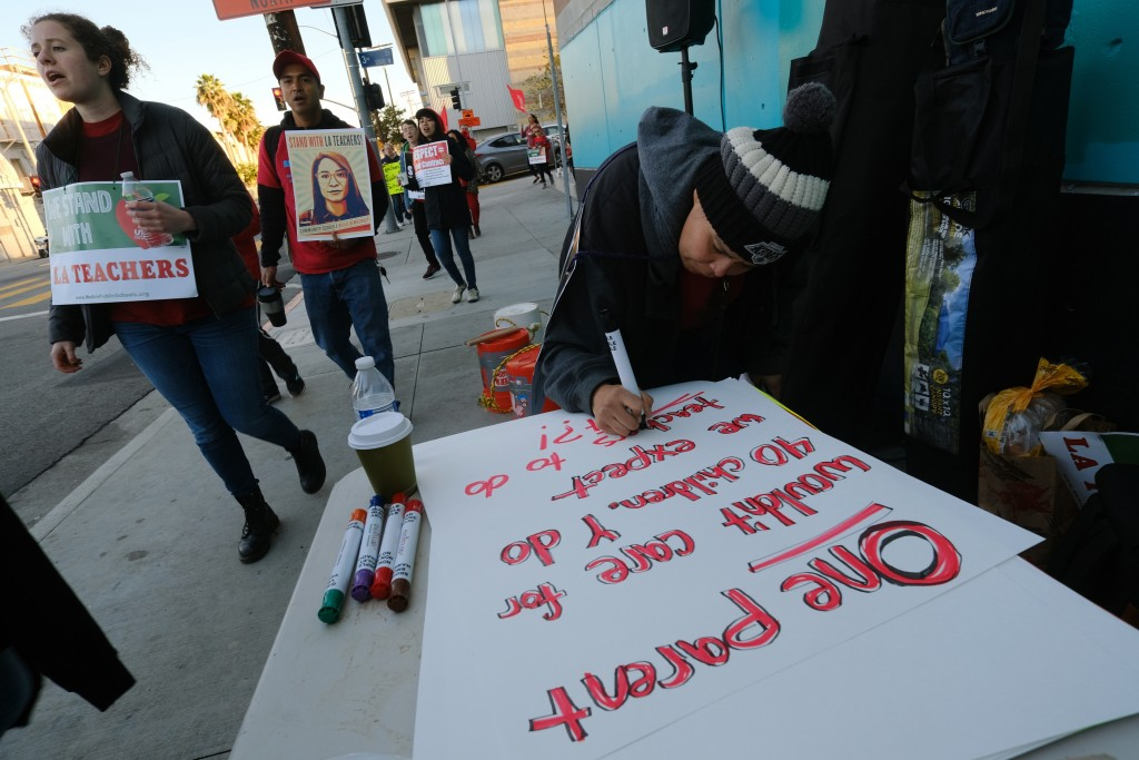 Rosa Companioni prepares a rally sign in support of Los Angeles school teachers Tuesday, Jan. 22, 2019, in Los Angeles.  A strike by thousands of Los ...
