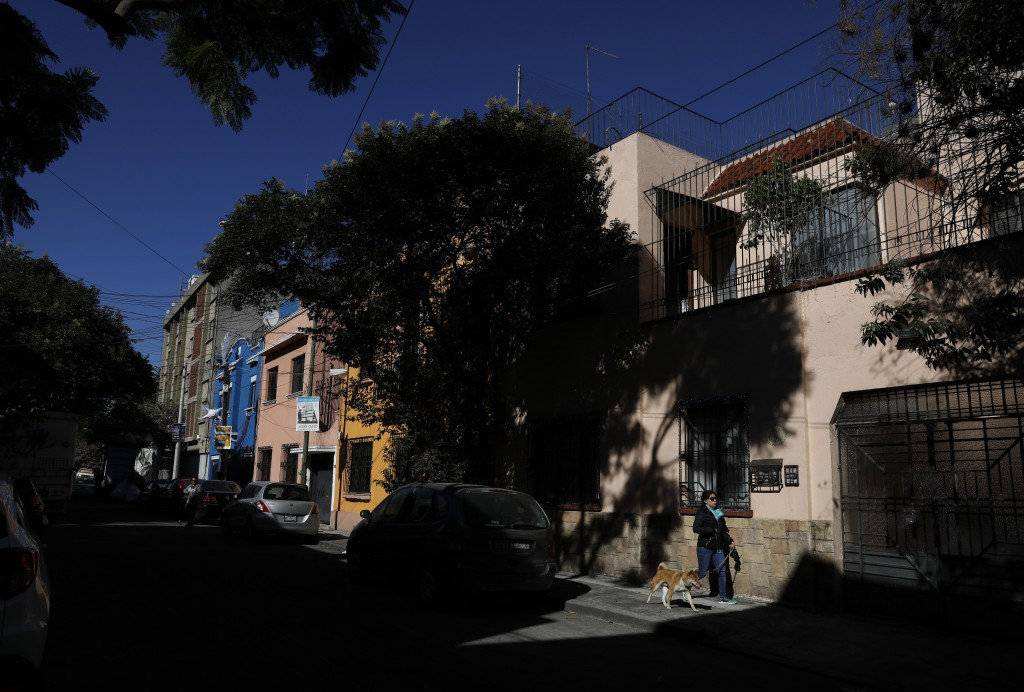 A woman walks her dog past the childhood home of film director Alfonso Cuaron, who lived here in the 1970s, on Tepeji Street in the Roma Sur neighborh