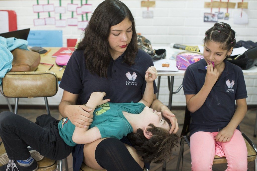 In this Dec.14, 2018 photo, transgender girls Angela, top left, plays with schoolmate Laura, as Violeta, right, sits next to them during a class break