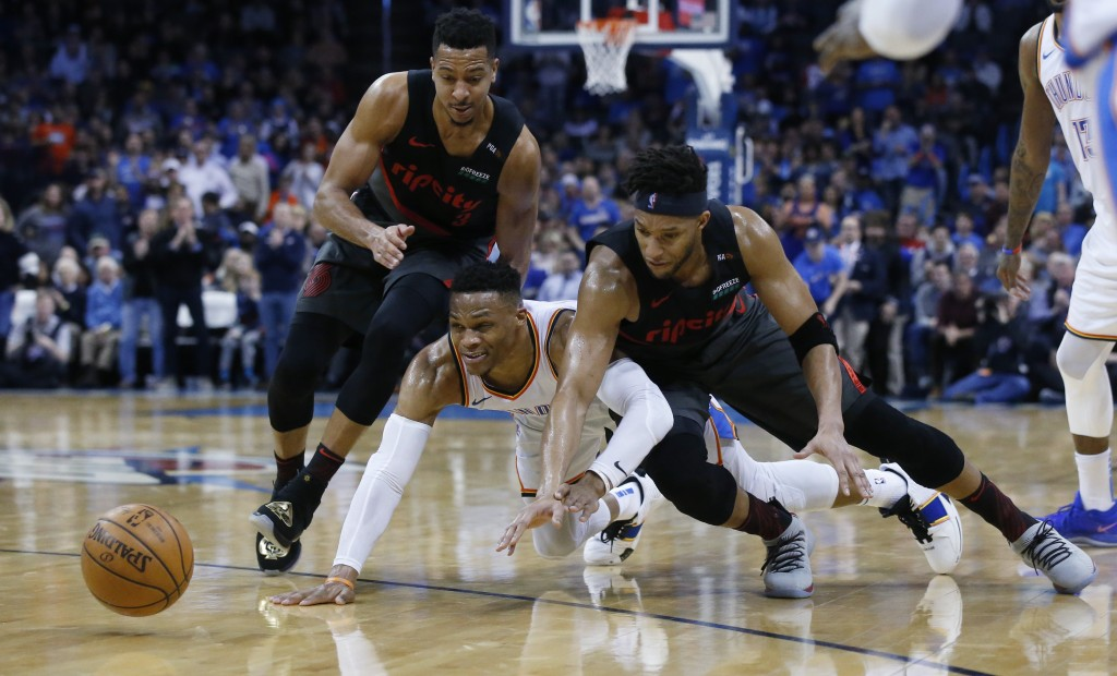Oklahoma City Thunder guard Russell Westbrook, center, Portland Trail Blazers guard C.J. McCollum, left, and guard Evan Turner, right, chase a loose b...